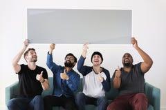 Ομάδα διαφορετικών φίλων που κάθονται στον καναπέ που κρατά τον κενό πίνακα στοκ εικόνα με δικαίωμα ελεύθερης χρήσης