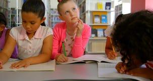 Ομάδα διαφορετικών schoolkids που μελετά μαζί στον πίνακα στη σχολική βιβλιοθήκη 4k απόθεμα βίντεο