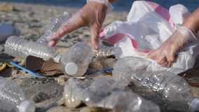 Ομάδα εθελοντών που καθαρίζουν επάνω τη γραμμή παραλιών Η γυναίκα αυξάνει και ρίχνει ένα πλαστικό μπουκάλι στην τσάντα απόθεμα βίντεο