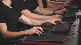 Ομάδα ενήλικων αρσενικών και θηλυκών gamers που κάθεται σε μια σειρά πίσω από τα όργανα ελέγχου, παιχνίδι στο κέντρο τυχερού παιχ απόθεμα βίντεο