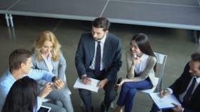 Ομάδα επιχειρηματιών που απασχολούνται μαζί στη συνεδρίαση του 'brainstorming' ομάδας Businesspeople φυλών μιγμάτων απόθεμα βίντεο