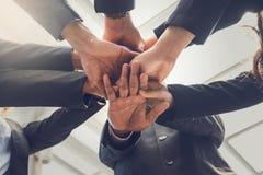 Ομάδα επιχειρηματιών που ενώνουν τα χέρια μαύρη ζωηρόχρωμη εργασία ομάδων κουκλών έννοιας ανασκόπησης στοκ εικόνα