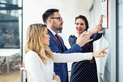 Ομάδα επιχειρηματιών που συζητούν το νέο πρόγραμμα για το whiteboard στοκ εικόνες