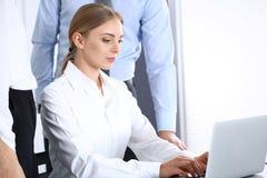 Ομάδα επιχειρηματιών που χρησιμοποιούν το φορητό προσωπικό υπολογιστή στεμένος στην αρχή Έννοια συνεδρίασης και ομαδικής εργασίας στοκ εικόνα