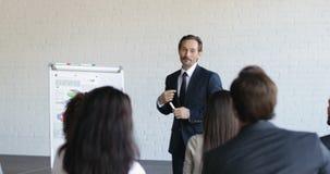 Ομάδα επιχειρηματιών στην παρουσίαση στη αίθουσα συνδιαλέξεων που ακούει τον επιτυχή κύκλο μαθημάτων κατάρτισης επιχειρηματιών απόθεμα βίντεο