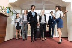 Ομάδα επιχειρηματιών συνεδρίασης των ρεσεψιονίστ ξενοδοχείων στο λόμπι Στοκ φωτογραφία με δικαίωμα ελεύθερης χρήσης