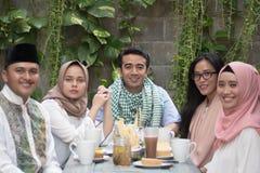 Ομάδα ευτυχούς νέου μουσουλμανικού έχοντας το υπαίθριο κοίταγμα γευμάτων στο έκκεντρο στοκ εικόνες