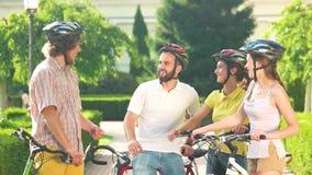 Ομάδα ευτυχών ποδηλατών που έχουν τη διασκέδαση στο πάρκο απόθεμα βίντεο