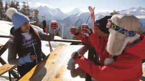 Ομάδα ευτυχών φίλων ενθαρρυντικών με το ποτό μετά από να κάνει σκι την ημέρα στον καφέ στο χιονοδρομικό κέντρο φιλμ μικρού μήκους