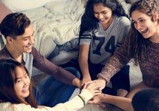 Ομάδα εφήβων σε μια κρεβατοκάμαρα που βάζει την έννοιά τους κοινοτήτων και ομαδικής εργασίας χεριών μαζί στοκ φωτογραφίες