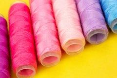 Ομάδα ζωηρόχρωμων στροφίων του νήματος που χρησιμοποιούνται στο ράψιμο, τη ραπτική και την κεντητική πέρα από το φωτεινό κίτρινο  στοκ εικόνα
