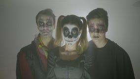Ομάδα θηλυκών και αρσενικών αποκριών zombies με τα κοστούμια και makeup στάση ακόμα και εξέταση τη κάμερα - απόθεμα βίντεο