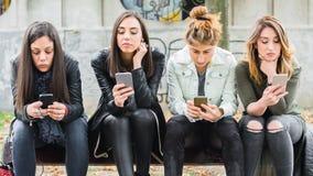 Ομάδα κοριτσιών που χρησιμοποιούν τα κινητά τηλέφωνα στον πάγκο πάρκων Στοκ φωτογραφία με δικαίωμα ελεύθερης χρήσης