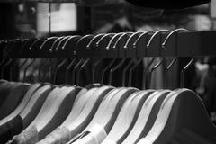 Ομάδα κρεμαστρών υφασμάτων στο ράφι πίσω και άσπρος Στοκ Φωτογραφία