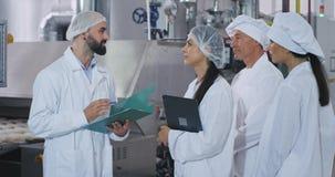 Ομάδα μηχανικού εργαζομένων βιομηχανίας αρτοποιείων που εξηγεί το σχέδιο της ασφάλειας του βιομηχανικού ηληκιωμένου αρτοποιών μηχ απόθεμα βίντεο