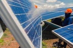 Ομάδα μηχανικών που εργάζεται στο ηλιακό πλαίσιο αντικατάστασης στη ηλιακή ενέργεια στοκ εικόνες