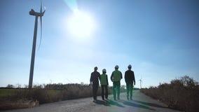 Ομάδα μηχανικών που περπατούν κατά μήκος του δρόμου στο αιολικό πάρκο απόθεμα βίντεο