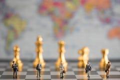 Ομάδα μικροσκοπικών επιχειρηματιών που περπατούν στον πίνακα σκακιού Στοκ Εικόνες