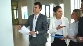 Ομάδα νέων επιχειρηματιών που μιλούν και που συζητούν την εργασία φιλμ μικρού μήκους