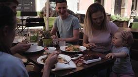 Ομάδα νέων με τα παιδιά που έχουν το μεσημεριανό γεύμα σε έναν καφέ στην οδό απόθεμα βίντεο