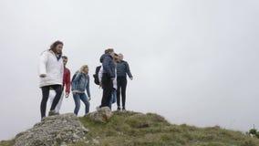 Ομάδα νέων οδοιπόρων με τα σακίδια πλάτης που στέκονται με τα χέρια που επιτυγχάνουν επάνω την κορυφή της έννοιας βουνών των νικη φιλμ μικρού μήκους