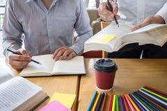 Ομάδα νέων που μαθαίνουν μελετώντας το νέο μάθημα στη γνώση στη βιβλιοθήκη κατά τη διάρκεια της βοήθειας της εκπαίδευσης φίλων δι στοκ εικόνες με δικαίωμα ελεύθερης χρήσης