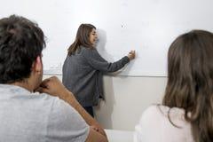 Ομάδα νέων σπουδαστών που παίρνουν το μάθημα στην πανεπιστημιακή τάξη με τη στάση κοριτσιών στην εξήγηση πινάκων και τους μαθητές Στοκ Φωτογραφία