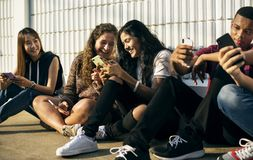 Ομάδα νέων φίλων εφήβων που καταψύχουν έξω μαζί να χρησιμοποιήσει την κοινωνική έννοια μέσων smartphone στοκ εικόνες με δικαίωμα ελεύθερης χρήσης