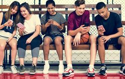 Ομάδα νέων φίλων εφήβων σε ένα γήπεδο μπάσκετ που χαλαρώνει χρησιμοποιώντας το smartphone στοκ εικόνες