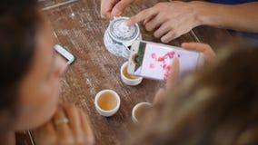 Ομάδα νέων φίλων που πίνουν το κινεζικό τσάι στον καφέ και που χρησιμοποιούν τις κινητές τηλεφωνικές συσκευές 4K φιλμ μικρού μήκους