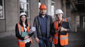 Ομάδα ομάδας επιθεωρητών ανδρών μηχανικών και δύο γυναικών που φαίνεται κάμερα στο πλαίσιο της αρχιτεκτονικής οικοδόμησης κατασκε απόθεμα βίντεο