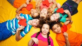 Ομάδα παιδιών που βάζουν με τις κόκκινες καρδιές Στοκ φωτογραφία με δικαίωμα ελεύθερης χρήσης