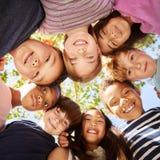 Ομάδα παιδιών που εξετάζουν υπαίθρια κάτω τη κάμερα, τετραγωνικό σχήμα στοκ εικόνες