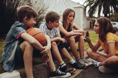 Ομάδα παιδιών που κάθονται μαζί και που μιλούν στοκ εικόνα