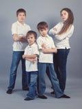 Ομάδα παιδιών στα τζιν στην γκρίζα ανασκόπηση Στοκ Φωτογραφίες