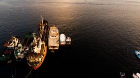 Ομάδα παλαιών φορτηγών πλοίων, Tugboats, σκαφών αλιείας και μικρών βαρκών στην ακτή κοντά στους βράχους Στοκ Εικόνα