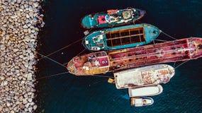 Ομάδα παλαιών φορτηγών πλοίων, Tugboats, σκαφών αλιείας και μικρών βαρκών στην ακτή κοντά στους βράχους Στοκ εικόνα με δικαίωμα ελεύθερης χρήσης