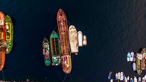 Ομάδα παλαιών φορτηγών πλοίων, Tugboats, σκαφών αλιείας και μικρών βαρκών στην ακτή κοντά στους βράχους Στοκ Φωτογραφίες