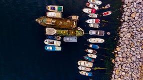 Ομάδα παλαιών φορτηγών πλοίων, Tugboats, σκαφών αλιείας και μικρών βαρκών στην ακτή κοντά στους βράχους Στοκ Εικόνες