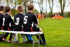 Ομάδα ποδοσφαίρου παιδιών σε έναν πάγκο Νέοι φορείς ομάδας ποδοσφαίρου Νέα αγόρια στα μαύρα πουκάμισα ως ποδοσφαιριστές υποκατάστ Στοκ Εικόνα