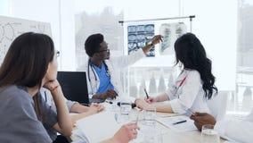 Ομάδα πολυ-εθνικού των επαγγελματικών γιατρών που συζητούν τις των ακτίνων X τυπωμένες ύλες του ασθενή στην κλινική Υγεία, νοσοκο φιλμ μικρού μήκους