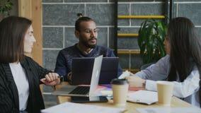 Ομάδα πολυ εθνικών ανθρώπων που κάθονται στο γραφείο με τα lap-top που λειτουργούν και που μιλούν για το νέο πρόγραμμα ξεκινήματο απόθεμα βίντεο