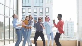 Ομάδα πολυ εθνικών νεαρών που καταψύχουν στο αστικό υπαίθριο υπόβαθρο απόθεμα βίντεο