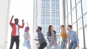 Ομάδα πολυ εθνικών νεαρών που καταψύχουν στο αστικό υπαίθριο υπόβαθρο φιλμ μικρού μήκους