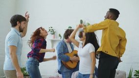 Ομάδα πολυ εθνικών φίλων που χορεύουν ενώ κιθάρα παιχνιδιού νεαρών άνδρων και κατοχή του εγχώριου κόμματος στο εσωτερικό φιλμ μικρού μήκους