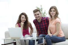 Ομάδα σπουδαστών που κάθονται σε έναν καναπέ πίσω από ένα τραπεζάκι σαλονιού Στοκ Εικόνες