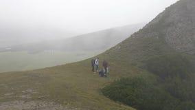 Ομάδα σπουδαστών στο ταξίδι ελεύθερου χρόνου που απολαμβάνει πεζοπορία στο βουνό που θαυμάζει τη φύση και που χαλαρώνει στη χλόη  φιλμ μικρού μήκους