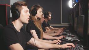 Ομάδα συγκεντρωμένων ανθρώπων στα ακουστικά που απολαμβάνουν το σε απευθείας σύνδεση τηλεοπτικό παιχνίδι στους υπολογιστές του κέ απόθεμα βίντεο