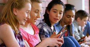 Ομάδα σχολικών φίλων που χρησιμοποιούν το κινητό τηλέφωνο 4k απόθεμα βίντεο