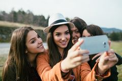 Ομάδα τεσσάρων νέων γυναικών υπαίθρια στοκ εικόνες